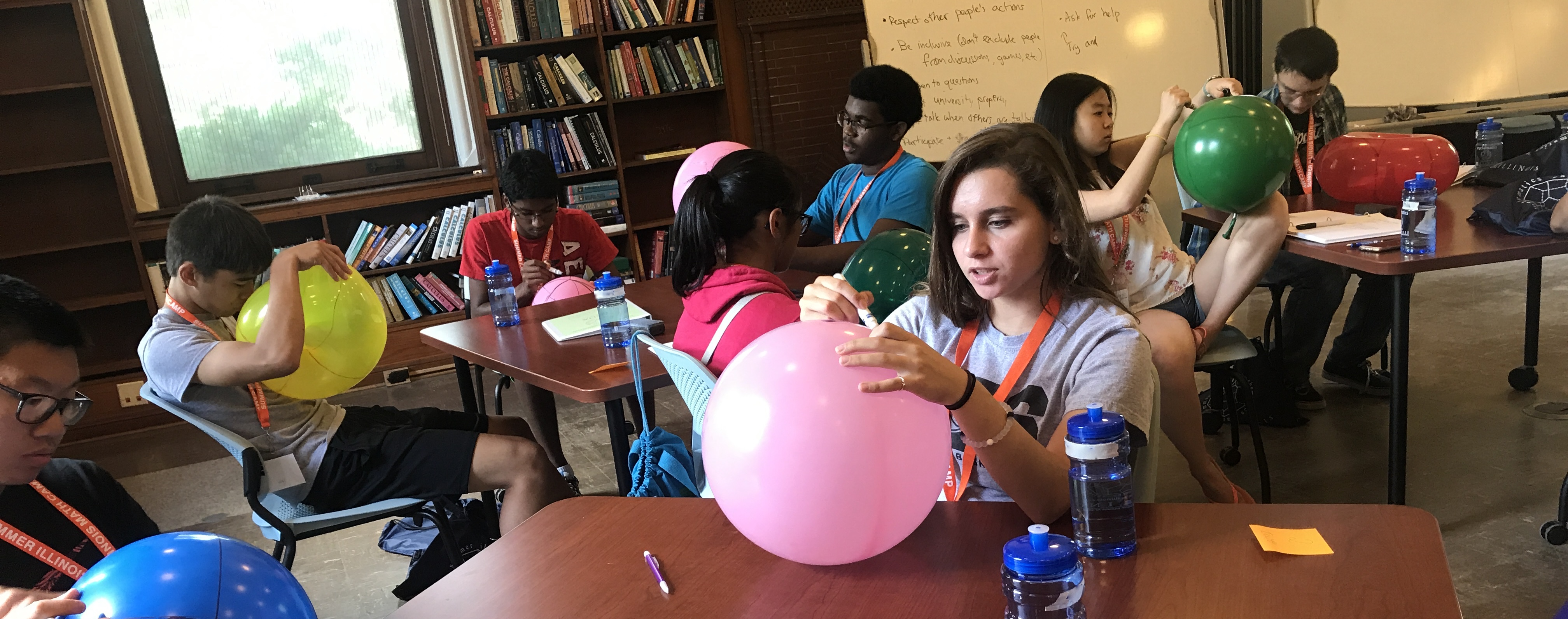 Campers drawing on balloons